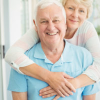 Portrait of happy senior couple smiling while hugging at home